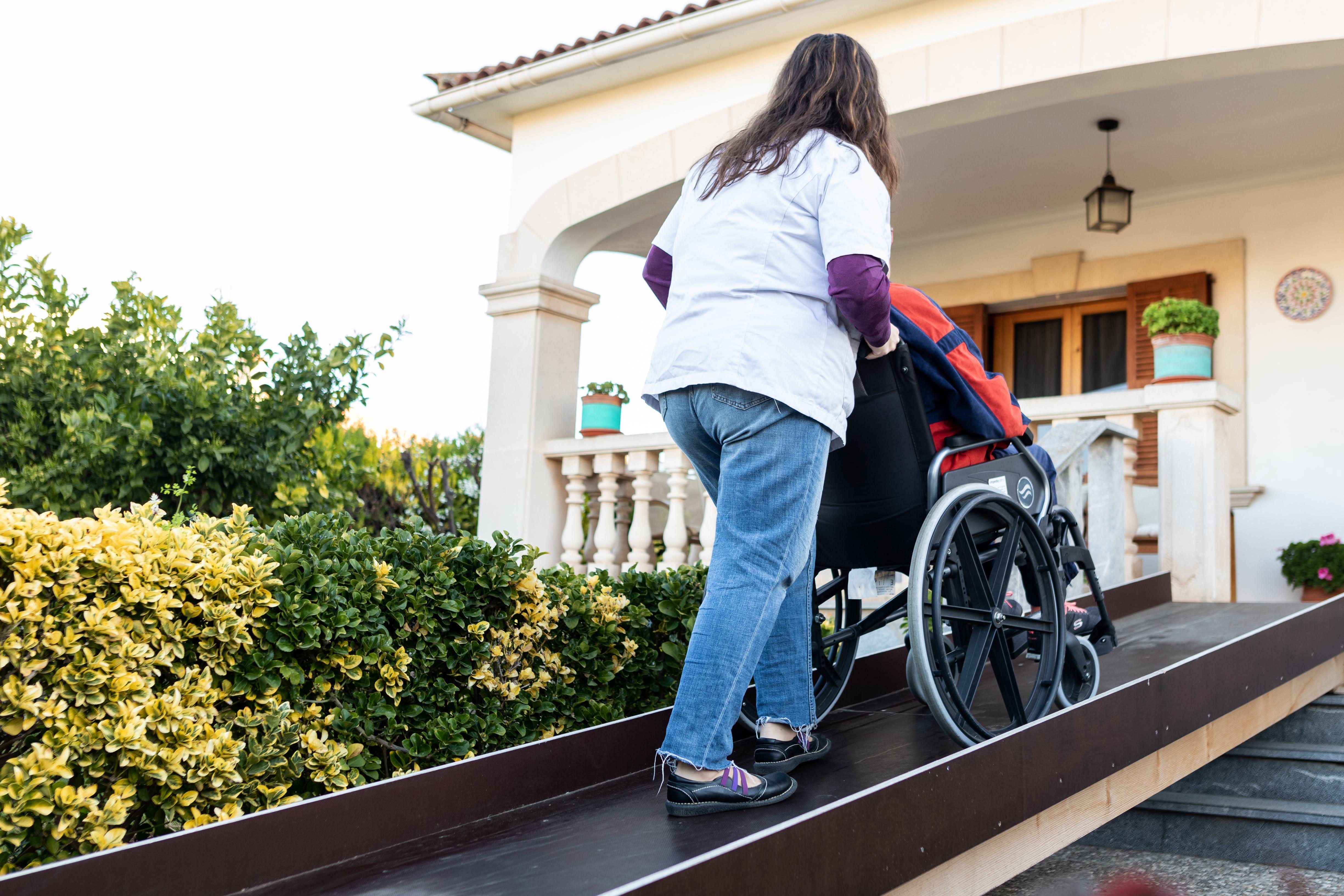 persona adulta en silla de rueda con su cuidadora