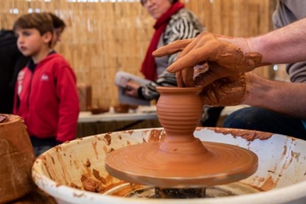manos dando molde a una vasija de barro y personas caminando en el fondo