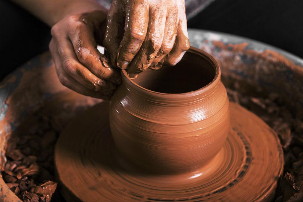manos dando molde a una vasija de barro