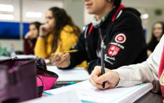 Personas escribiendo notas en sus libretas durante una clase